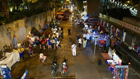 Night passage, vendor stalls at sides, BTS Saphan Taksin station, high angle Footage