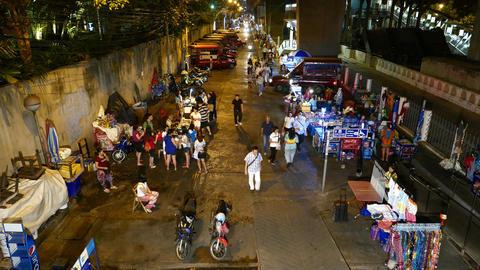 Night passage, vendor stalls at sides, BTS Saphan Taksin station, high angle Live Action