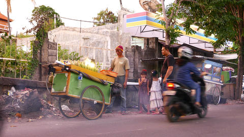 Fry corn cooking wheel cart on busy street, small girls with father waiting Footage