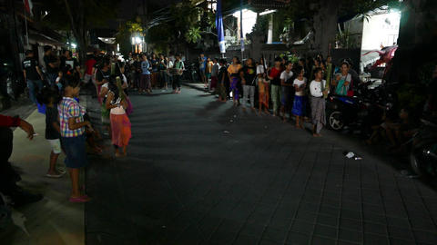 Balinese children stand in row at dark backstreet, parade rehearsal Footage