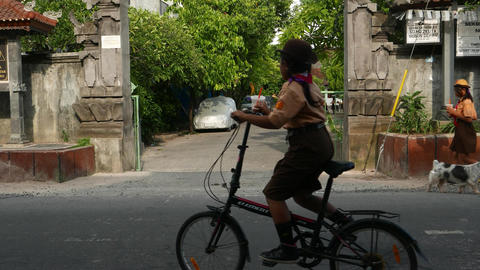 School girls in uniform on bicycle cross street and ride to schoolyard Footage