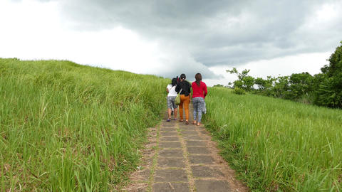 Balinese girls walk on Campuhan Ridge Walk, tiled path on top of grassy hill Footage