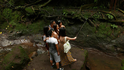 Asian tourist make group selfie on smartphone use extension stick for wide angle Footage