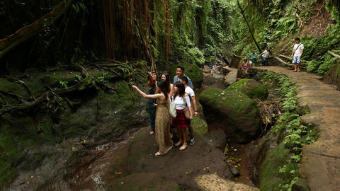 Tourist group prepare to take selfie picture at bottom of rocky gorge Footage