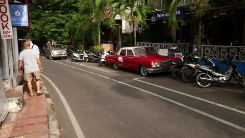 Red Chevrolet Biscayne parked at alley against restaurant on Bali Footage