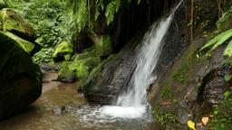 Small waterfall rush down rocky landscape, fallen mossy boulders Footage