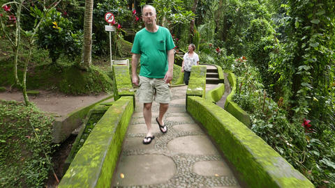 Senior tourist come towards camera, small stony bridge ancient tropical park Footage