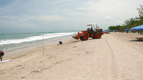 Man Clean Surfboarding Beach, Drop Small Wood Into Tractor Bucket stock footage