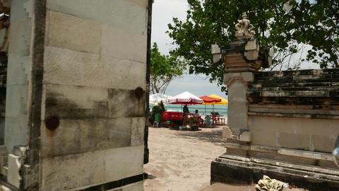 FPV Walk Through Small Stone Gate To Kuta Beach, Glide Shot stock footage