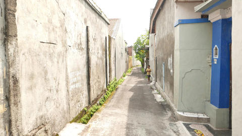 Walk through narrow alley, towards little indonesian boy, sunny day Footage