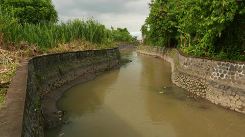 Stone walled canal banks, unnamed river near with Jl Gn Soputan bridge Footage