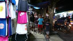 Walking boys pose on camera, night shopping street, Kuta Footage