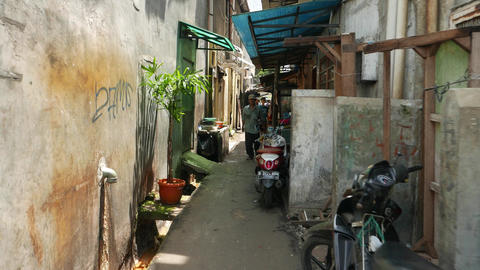 FPV come through narrow alley, people ahead, fat boy with smartphone Footage