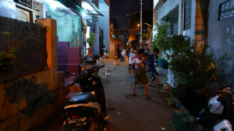 Little boys play football game on dark alley, night slumming, glide shot Footage