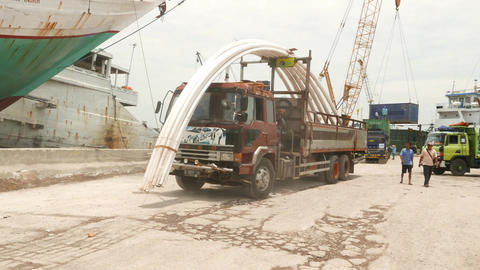 Small truck loaded with curved steel pillars, maneuring in dusty port Footage