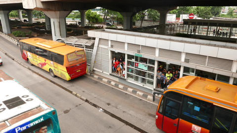 Yellow-orange Transjakarta bus departs from stop, next bus pass by without stop Live Action