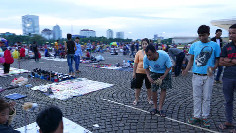Locals play ring toss game, Merdeka Square, parallax shot Footage