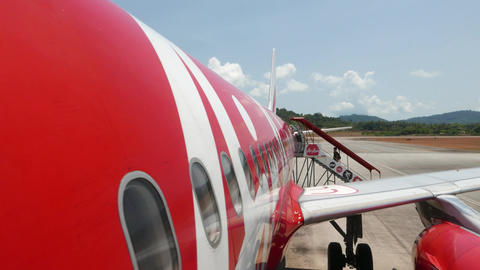 Entering AirAsia airplane, passenger POV view, red white aircraft hull Footage
