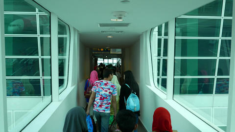 Passenger crowd walk through jet bridge, enter arrival gate hall Footage
