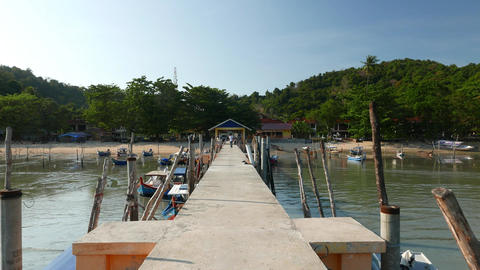 Walk to shore by fishing pier, boats mooring, tropical island scenery Footage