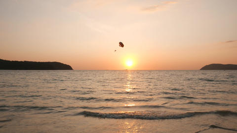 Parasail parachute fly against beautiful tropical island sunset, sea water Footage