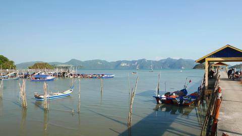 Tropical island fishing boat moorage quay, panoramic shot, panning view Footage