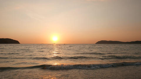 Tropical island sunset, clear sky, sea waves, sun disc, horizon view Live Action
