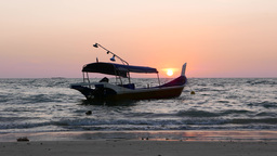 Fishing boat beach sunset, backlit, telephoto view, shallow water Footage