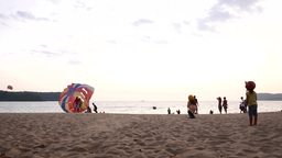 Two Little Girls In Helmets Look On Parasail Canopy Landing, Then Run Away stock footage