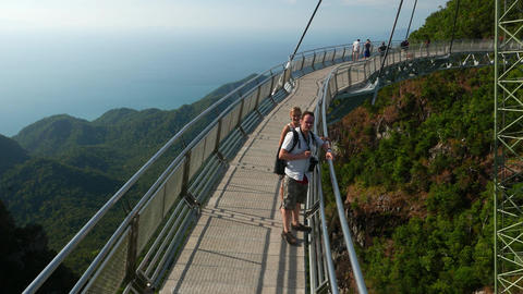 European tourist couple on aerial curved bridge, observation deck, Langkawi Footage