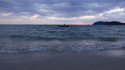 Purple cloudy sky, twilight beach view, motor boat manures on sea water Footage