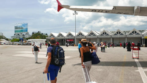 Couple walk out airplane, island airport, vacation time, follow camera Footage