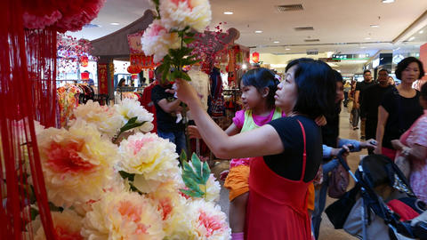 Asian woman with daughter choosing artificial chrysanthemum flower Footage