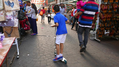 Boy on push-cycle struggle through crowd on market street, follow behind Footage