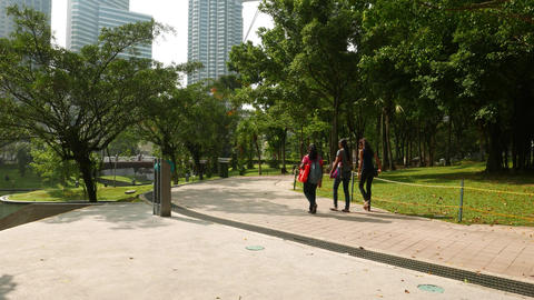 Three young indian girls walk in park, sunny day, first Petronas tower on back Footage