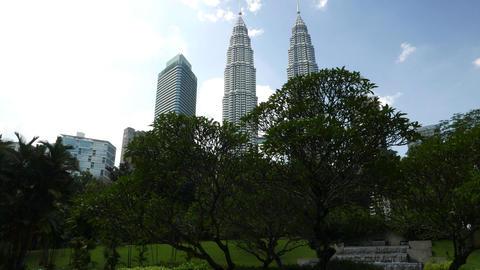 Long panning shot of beautiful Petronas Twin Towers behind park trees Footage