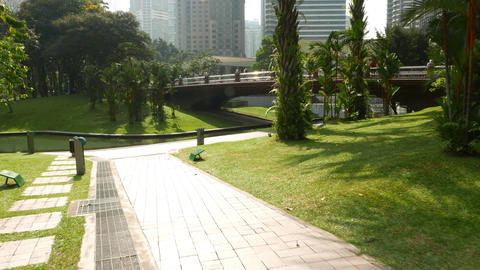 Sunny modern city park pathway, walking forward, look up to Petronas Twin Towers Footage