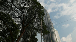 Long panning dolly shot Menara Petronas, hiding behind tree crown Footage