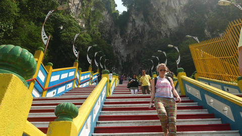 Climb up staircase to Batu Caves entrance, european tourists come down Footage