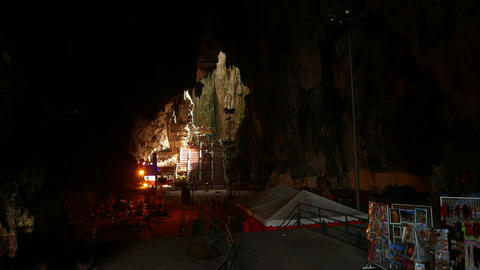 Walking through mystical Batu Caves, dark chamber and bright area ahead Footage