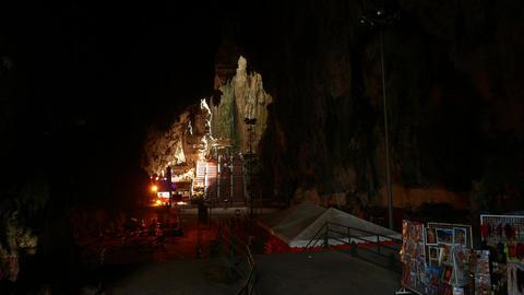 Walking through mystical Batu Caves, dark chamber and bright area ahead Footage