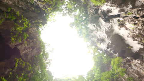 Rotating in the middle of the cave floor, beautiful opening view up blazing sky Footage