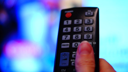 Remote control. Thumb touching the channel button on a remote control Footage