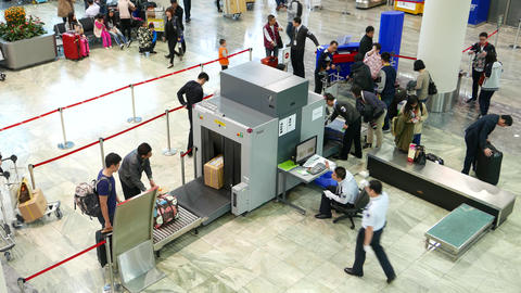 Box stuck at security scanner input tape, officer give directions Footage