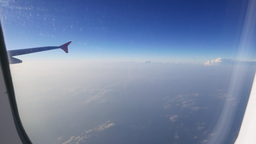 Looking out of the plane through window, small clouds blue sky, plane wing Live Action