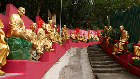 Gold Buddha statues on the way to temple, moving up on the staircase Footage