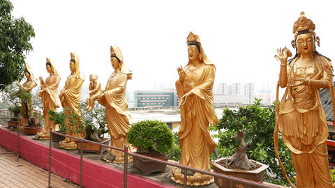 Standing gold statues, Buddhist temple, hillside and city on background Footage