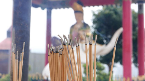 Bunch of incense sticks burning with smoke, somebody put more sticks Live Action