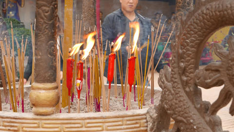 Close up incense sticks and burning candles, daytime, Buddhist temple Footage