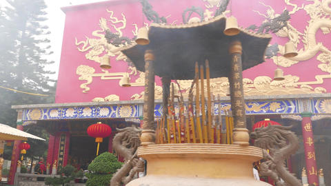 Bowl full of smouldering incense sticks in front of main shrine, buddhist temple Footage